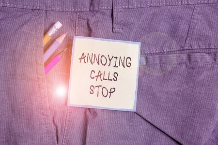 Text sign showing Annoying Calls Stop. Business photo showcasing Prevent spam phones Blacklisting numbers Angry caller Writing equipment and green note paper inside pocket of man work trousers