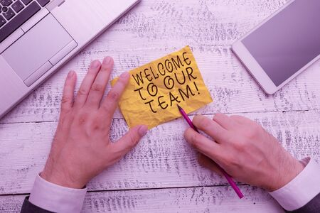 Text sign showing Welcome To Our Team. Business photo text introducing another demonstrating to your team mates Hand hold note paper near writing equipment and modern smartphone device