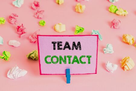 Writing note showing Team Contact. Business concept for The interaction of the individuals on a team or group Colored crumpled papers empty reminder pink floor background clothespin Banco de Imagens
