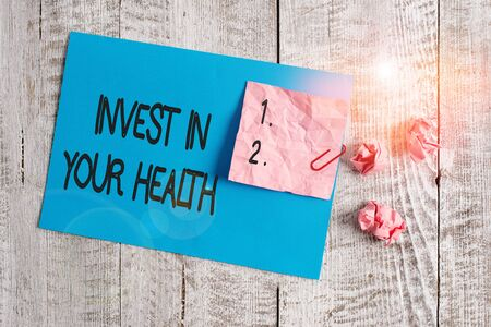 Word writing text Invest In Your Health. Business photo showcasing Live a Healthy Lifestyle Quality Food for Wellness Wrinkle paper and cardboard plus stationary placed above wooden background