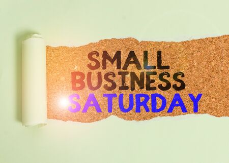 Writing note showing Small Business Saturday. Business concept for American shopping holiday held during the Saturday Cardboard which is torn placed above a wooden classic table