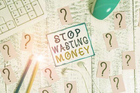 La scrittura della nota mostra smettere di sprecare denaro. Il concetto di business per l'organizzazione del programma di gestione consente di iniziare ora strumenti di scrittura e carta scarabocchiata sulla parte superiore del tavolo di legno