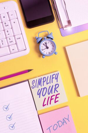 Writing note showing Simplify Your Life. Business concept for Manage your day work Take the easy way Organize White paper with copy space with paper clips clock and pc keyboard