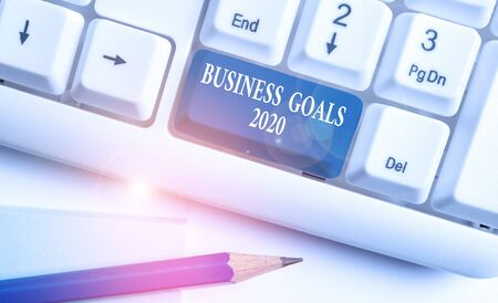 Conceptual hand writing showing Business Goals 2020. Concept meaning Advanced Capabilities Timely Expectations Goals White pc keyboard with note paper above the white background