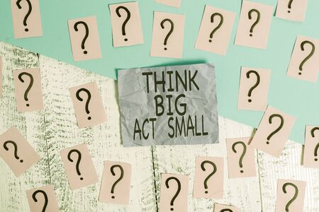 Text sign showing Think Big Act Small. Business photo showcasing Great Ambitious Goals Take Little Steps one at a time Scribbled and crumbling papers with thick cardboard above wooden table Stok Fotoğraf