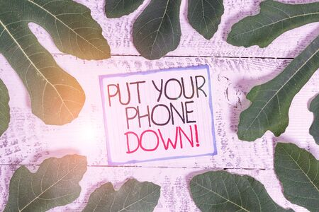 Handwriting text Put Your Phone Down. Conceptual photo end telephone connection saying goodbye caller Leaves surrounding notepaper above a classic wooden table as the background