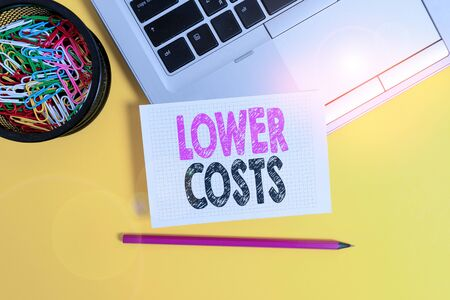 Conceptual hand writing showing Lower Costs. Concept meaning the business sets low price to enhance theproduct deanalysisd Trendy laptop pencil squared paper container colored background