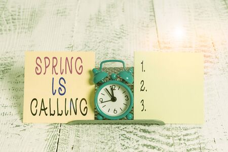 Writing note showing Spring Is Calling. Business concept for Time for flowers March coming beautiful colors Sunny Mini blue alarm clock standing above buffer wire between two paper