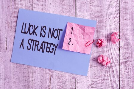 Word writing text Luck Is Not A Strategy. Business photo showcasing it is not being Lucky when planned intentionally Wrinkle paper and cardboard plus stationary placed above wooden background