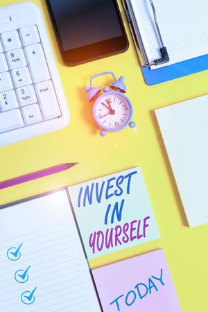 Writing note showing Invest In Yourself. Business concept for Improve your Skills take courses Do masters Scholarship White paper with copy space with paper clips clock and pc keyboard