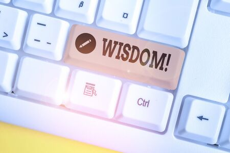 Text sign showing Wisdom. Business photo showcasing the ability to use your knowledge and experience to make decisions White pc keyboard with empty note paper above white background key copy space