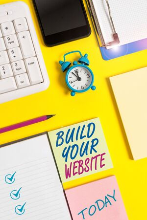 Writing note showing Build Your Website. Business concept for Setting up an ecommerce system to market a business White paper with copy space with paper clips clock and pc keyboard