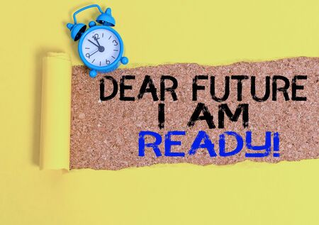Handwriting text writing Dear Future I Am Ready. Conceptual photo state action situation being fully prepared Alarm clock and torn cardboard placed above a wooden classic table backdrop Banco de Imagens