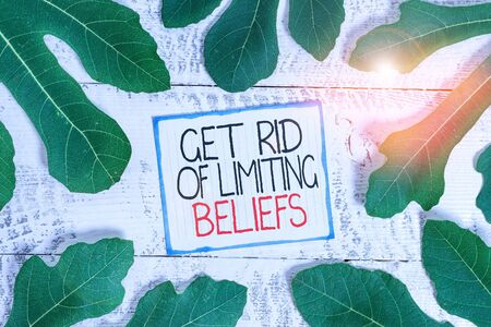 Handwriting text Get Rid Of Limiting Beliefs. Conceptual photo remove negative beliefs and think positively Leaves surrounding notepaper above a classic wooden table as the background