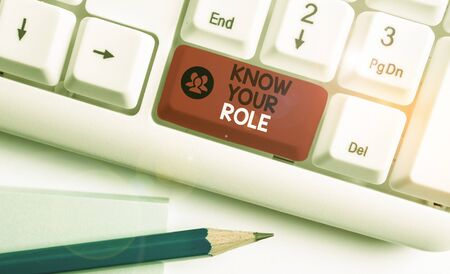 Writing note showing Know Your Role. Business concept for end acting outside who you actually are Play your position White pc keyboard with note paper above the white background