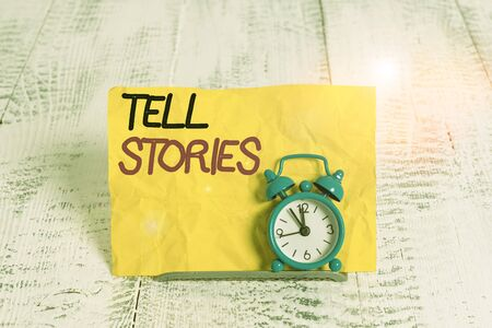 Word writing text Tell Stories. Business photo showcasing formal to tell someone about something that has happened Mini blue alarm clock stand tilted above buffer wire in front of notepaper