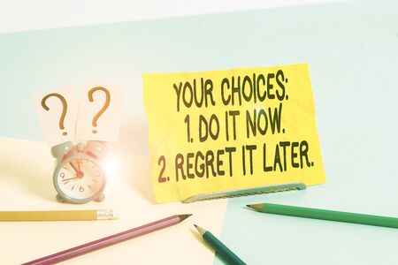 Text sign showing Your Choices 1 Do It Now 2 Regret It Later. Business photo text Think first before deciding Mini size alarm clock beside stationary placed tilted on pastel backdrop