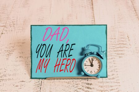 Conceptual hand writing showing Dad You Are My Hero. Concept meaning Admiration for your father love feelings compliment Alarm clock tilted above buffer wire in front of notepaper