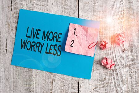 Word writing text Live More Worry Less. Business photo showcasing Have a good attitude motivation be careless enjoy life Wrinkle paper and cardboard plus stationary placed above wooden background