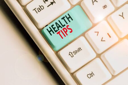 Writing note showing Health Tips. Business concept for beneficial to one s is physical mental or emotional state White pc keyboard with note paper above the white background