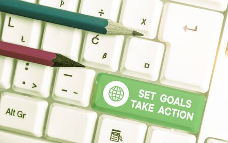 Writing note showing Set Goals Take Action. Business concept for Act on a specific and clearly laid out plans White pc keyboard with note paper above the white background Archivio Fotografico