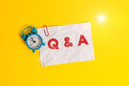 Text sign showing Q And A. Business photo showcasing a period of time or an occasion when someone answers questions Metal alarm clock clip blank crushed note sheet colored background Reklamní fotografie