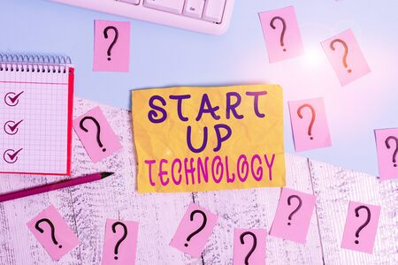 Writing note showing Start Up Technology. Business concept for Young Technical Company initially Funded or Financed Writing tools and scribbled paper on top of the wooden table