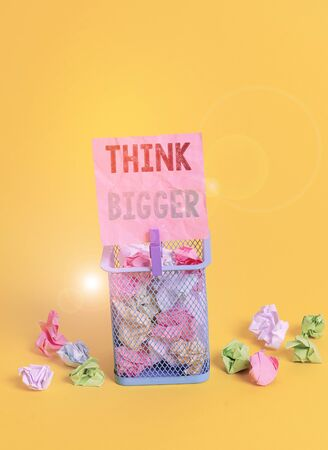 Handwriting text writing Think Bigger. Conceptual photo being able to dream and visualise what you can achieve Trash bin crumpled paper clothespin empty reminder office supplies yellow