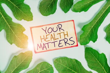Text sign showing Your Health Matters. Business photo showcasing Physical Wellness is Important Stay Fit and Healthy Leaves surrounding notepaper above an empty soft pastel table as background Stock Photo