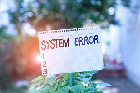 Text sign showing System Error. Business photo showcasing instruction that is not recognized by an operating system Plain empty paper attached to a stick and placed in the green leafy plants