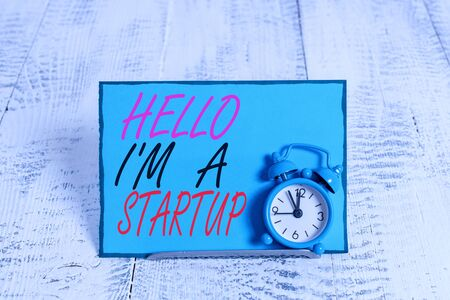 Conceptual hand writing showing Hello I M A Startup. Concept meaning Entrepreneur starting business Presenting New project Alarm clock tilted above buffer wire in front of notepaper Reklamní fotografie