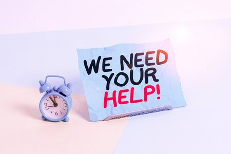Writing note showing We Need Your Help. Business concept for asking someone to stand with you against difficulty Alarm clock beside a Paper sheet placed on pastel backdrop Фото со стока