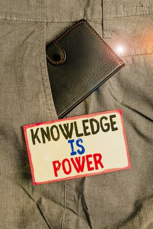 Conceptual hand writing showing Knowledge Is Power. Concept meaning skills acquired through experience and education Small wallet inside trouser front pocket near notation paper