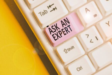 Text sign showing Ask An Expert. Business photo showcasing consult someone who has skill about something or knowledgeable White pc keyboard with empty note paper above white background key copy space