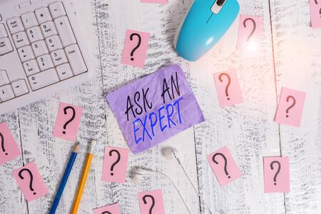 Writing note showing Ask An Expert. Business concept for consult someone who has skill about something or knowledgeable Writing tools and scribbled paper on top of the wooden table Stock Photo