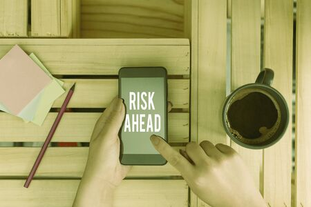 Conceptual hand writing showing Risk Ahead. Concept meaning A probability or threat of damage, injury, liability, loss woman with laptop smartphone and office supplies technology Standard-Bild - 133468539