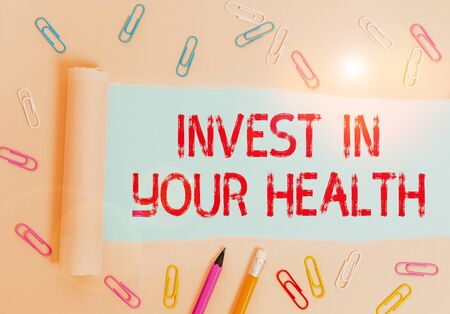 Writing note showing Invest In Your Health. Business concept for Live a Healthy Lifestyle Quality Food for Wellness Stationary and torn cardboard placed above plain pastel table backdrop