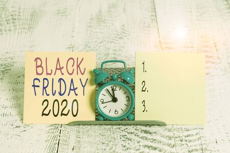 Writing note showing Black Friday 2020. Business concept for day following Thanksgiving Discounts Shopping day Mini blue alarm clock standing above buffer wire between two paper