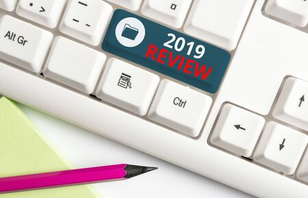 Writing note showing 2019 Review. Business concept for New trends and prospects in tourism or services for 2019 White pc keyboard with note paper above the white background
