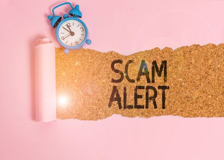 Text sign showing Scam Alert. Business photo showcasing unsolicited email that claims the prospect of a bargain Alarm clock and torn cardboard placed above a wooden classic table backdrop