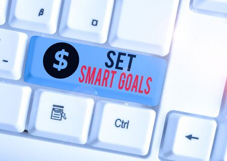 Writing note showing Set Smart Goals. Business concept for giving criteria to guide in the setting of objectives White pc keyboard with note paper above the white background