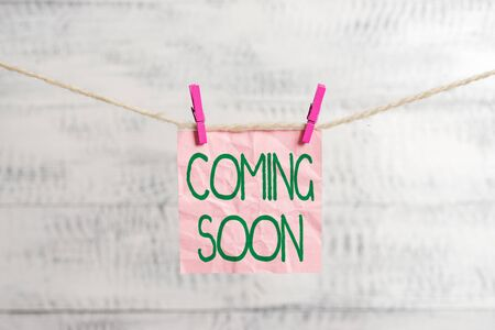 Conceptual hand writing showing Coming Soon. Concept meaning something is going to happen soon or after a short time Clothespin rectangle shaped paper reminder white wood desk
