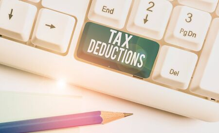 Text sign showing Tax Deductions. Business photo showcasing an amount or cost that subtracted from someone s is income White pc keyboard with empty note paper above white background key copy space