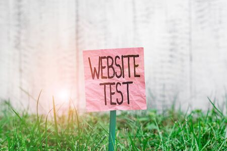 Conceptual hand writing showing Website Test. Concept meaning test the websites or web applications for potential bugs Plain paper attached to stick and placed in the grassy land