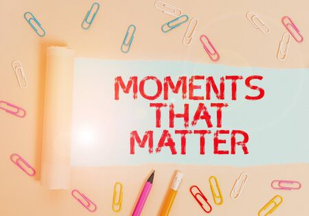 Writing note showing Moments That Matter. Business concept for Meaningful positive happy memorable important times Stationary and torn cardboard placed above plain pastel table backdrop