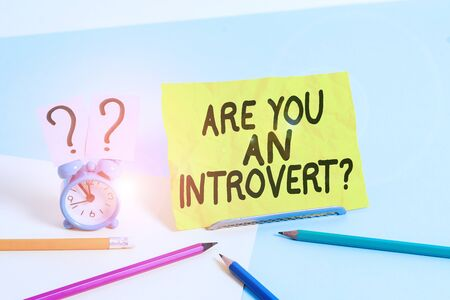Text sign showing Are You An Introvertquestion. Business photo text demonstrating who tends to turn inward mentally Mini size alarm clock beside stationary placed tilted on pastel backdrop