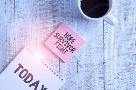 Word writing text Hope Survivor Fight. Business photo showcasing stand against your illness be fighter stick to dreams Stationary placed next to a cup of black coffee above the wooden table