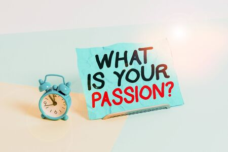 Writing note showing What Is Your Passion Question. Business concept for asking about his strong and barely controllable emotion Alarm clock beside a Paper sheet placed on pastel backdrop