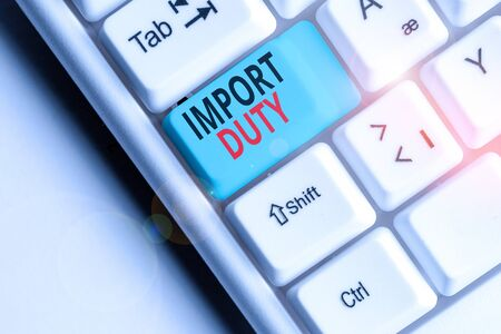 Writing note showing Import Duty. Business concept for tax imposed by a government on goods from other countries White pc keyboard with note paper above the white background Archivio Fotografico