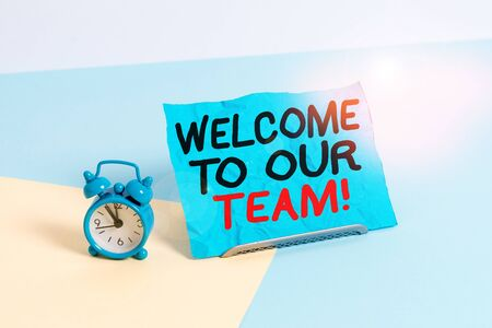 Writing note showing Welcome To Our Team. Business concept for introducing another demonstrating to your team mates Alarm clock beside a Paper sheet placed on pastel backdrop